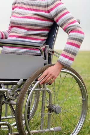 Wheel chair: Woman propelling wheelchair  Stock Photo