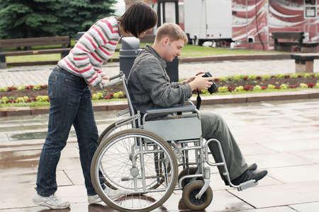 Joyful man auf einen Rollstuhl suchen Bild in der Kamera Standard-Bild - 5130040