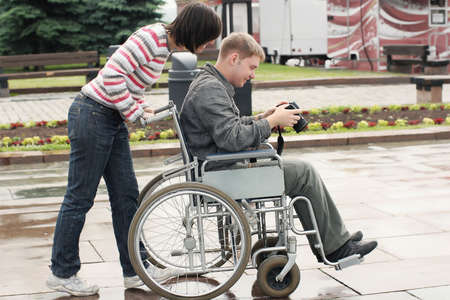Joyful man on a wheelchair looking image in the camera photo