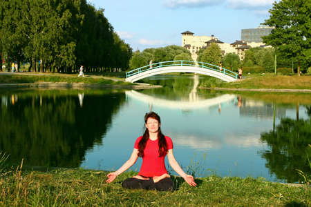 Beautiful young woman meditating in yoga pose outdoors. photo
