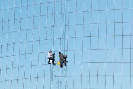 cleaning team: Trabajadores lavado de paneles de cristal de la torre de oficinas moderno.