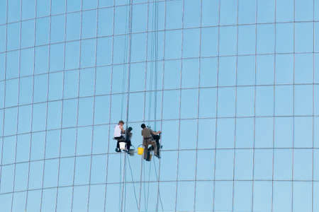 Workers washing glass panels of modern high-rise office tower.
