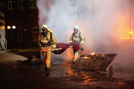 Firefighters carrying an accident victim from a fire.