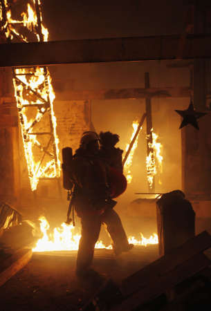house fire: A fireman carrying an accident victim Stock Photo