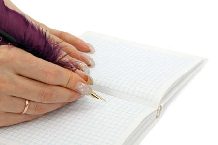 Female diary. The woman writes a feather to a writing-book photo