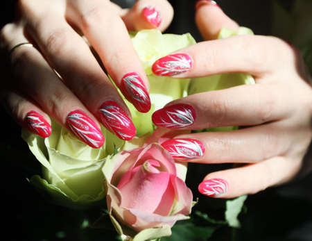 Beautiful nail design. Woman hands over  roses.