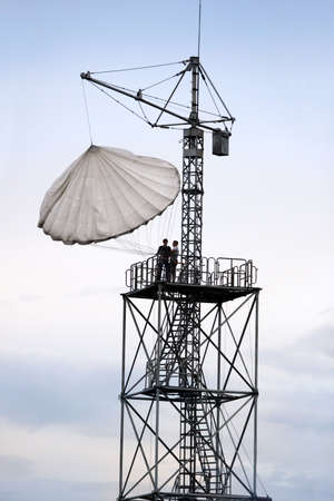 Training to parachute jumps on a special tower with instructor. photo