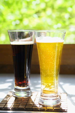 sapid: Two glasses of different flavour beer - light and dark on summer background.
