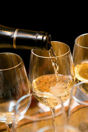 aligote: White wine pouring on glasses on a party. Black background
