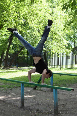 Young man is doing a workout in the city. Outdoor.  Summertime. photo
