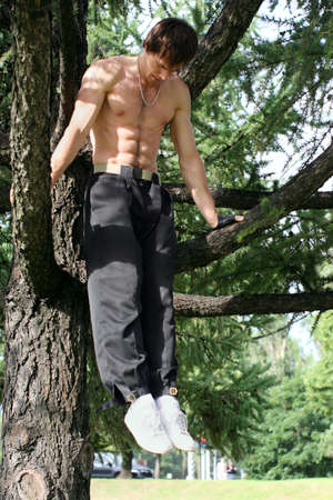 Young muscular man is doing a workout in the city park.  Summertime. photo