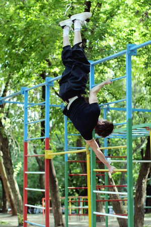 Workout.  Handstand on playground equipment bars. Summertime photo