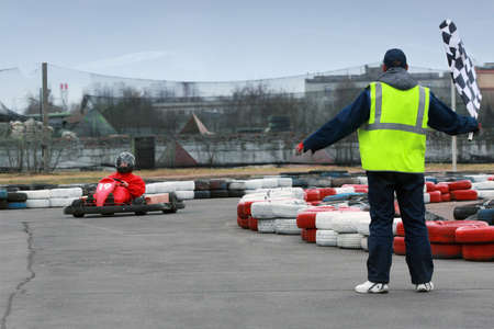 An amateur driver in a go-carts and man with race flag.  photo