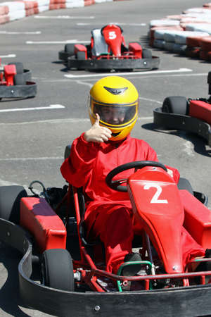 kart: A smiling young  racer shows ok. Go-carting Stock Photo