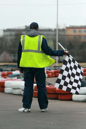 Worker with a rippled black and white flag on go-cart racing photo