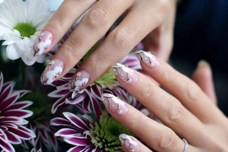 Beautiful nail design. Woman hands over flowers.