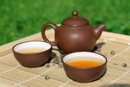 Green tea serving in clay tea pot and two cups photo