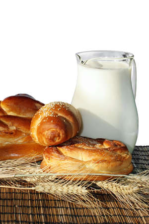 Baking bread, wheat ears and jug with milk on a bamboo mat.  photo