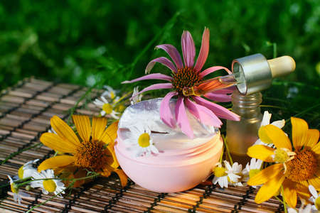 Essential oil  and box of natural cream with flowers  - beauty treatment