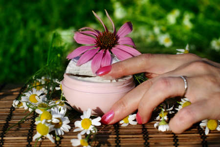 Female hand and  box of  cream with flowers. Stock Photo - 8041742