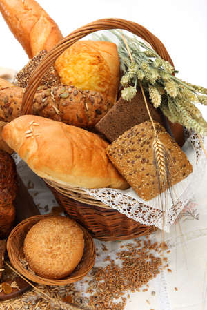 Different bread products  with ears of wheat and seeds in basket Stock Photo
