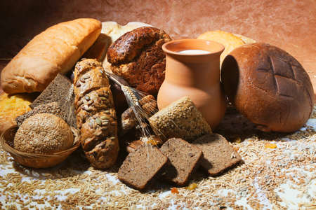 Still-life with  different bread products and jug of milk on brown classical background photo