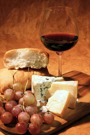 Still-life with cheese, grapes, italian ciabatta bread and glass of red wine. photo