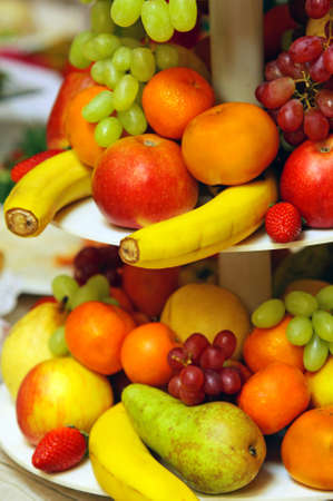 Assorted fresh fruit including bananas, tangerines, apples, grapes and pears  photo