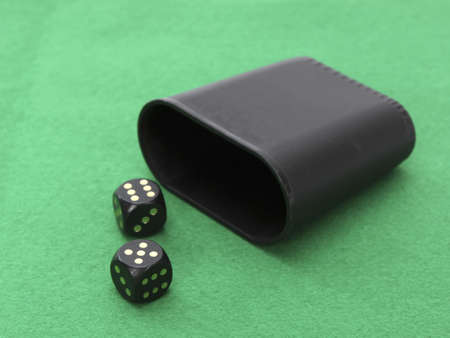 A dice with dice cup on a games green table. photo