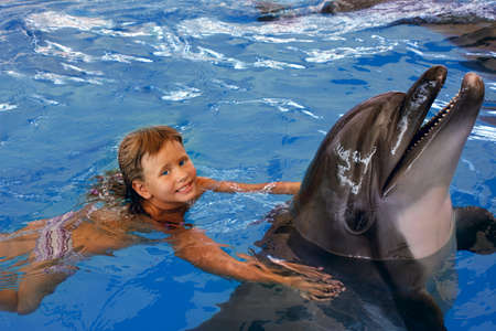dolphins: Happy child  and dolphin in blue water. Stock Photo