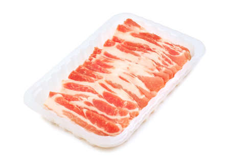 streaky: Raw bacon rashers in a plastic packaging tray isolated on white background.