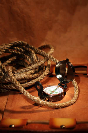Still-life with  compass, rope and leather roll over old paper. Travel or vacation concept photo