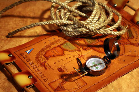 Still-life with vintage leather map of South America, compass and rope over rough paper. Travel concept photo