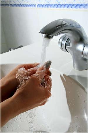 lavarse las manos: Lavarse las manos en el baño con agua caliente Foto de archivo