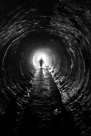 tunel: silueta en un túnel de comunicación a la luz final del túnel