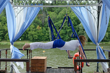 Female Aerial Acrobat Relaxing  Yoga in a hammock photo