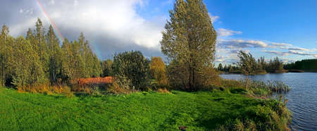 Picturesque autumn landscape with  river and bright  rainbow  over the woodland photo