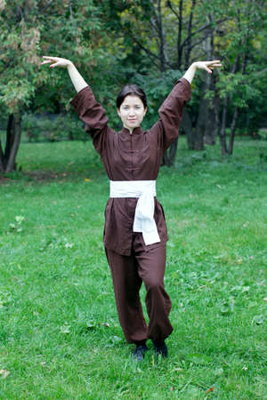 chi kung: Zen pretty woman practicing exercise chi kung, tai chi, kung fu or yoga in natural park