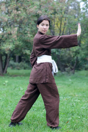 Zen pretty woman practicing exercise chi kung, tai chi or kung fu  in natural park photo
