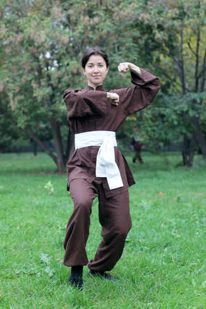 chi kung: Zen pretty woman practicing exercise chi kung, tai chi or kung fu  in natural park Stock Photo
