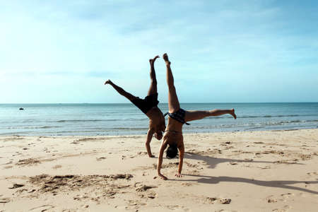 A sexy young man and women doing cartwheels on the beach photo