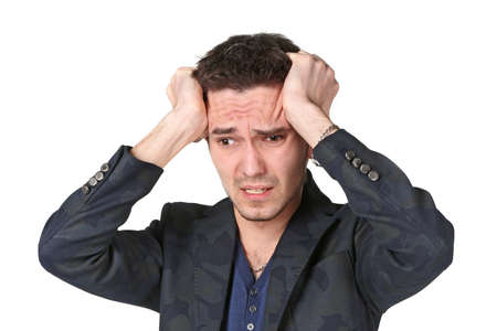 doldrums: Portrait of  upset young man grabbing his head in desperation over white background Stock Photo