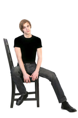 black t shirt: Handsome young  man in black clothes  sitting on a chair on white background Stock Photo