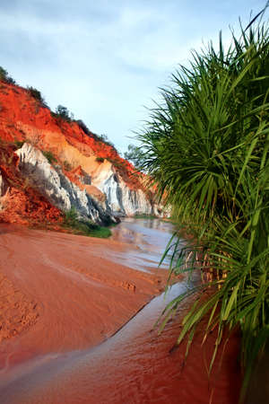 Landscape with river between red rocks and jungle  Ham Tien canyon  Mui ne, Vietnam photo