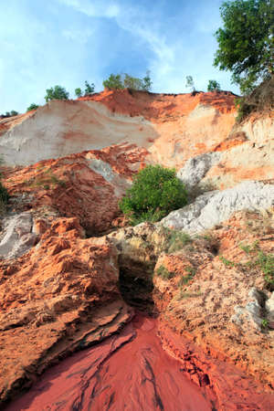 stratification: Ham Tien canyon in Vietnam, small stream carving through the sand