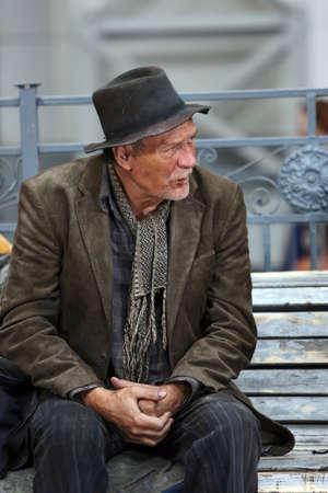 hombre solitario: Solitario hombre sin hogar de ancianos sentados en un banco en la calle