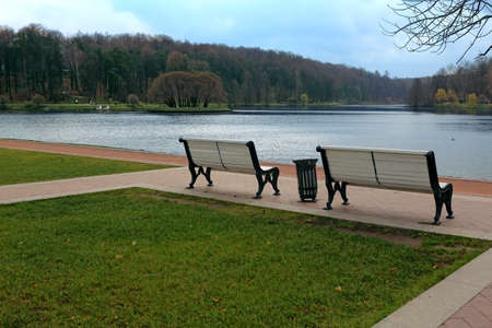 garden bench: Empty wooden benches overlooking a river in the  park  Moscow