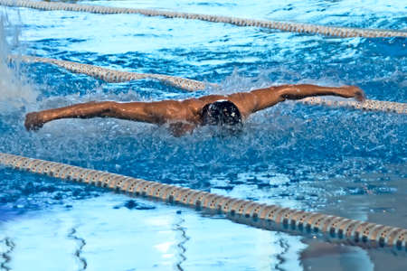 outdoor training: Young man in  cap swimming butterfly stroke style in the blue water pool Stock Photo