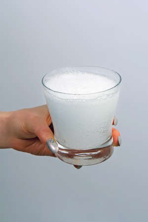 fizzy tablet: Glass with water and effervescent tablet in a female hand