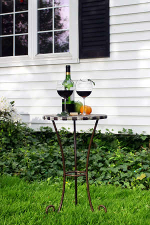 small table: Small table with a bottle of wine and glasses in  garden near house